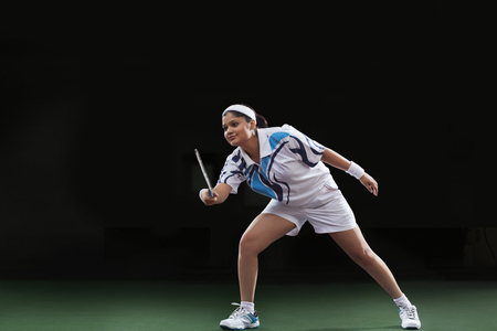 Young woman in sportswear playing badminton over black background