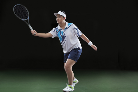 Young female player in sportswear playing tennis over black background