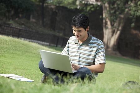 Estudiante con una computadora portátil que se sienta en un parque