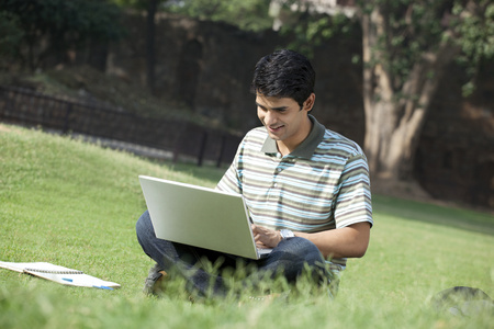 Student with a laptop sitting in a park Stock Photo