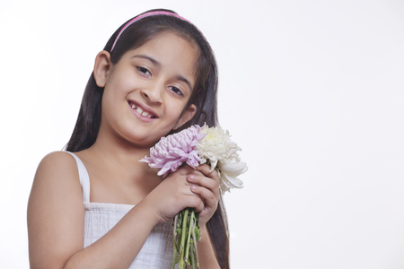 Portrait of a little girl holding flowers Stock Photo