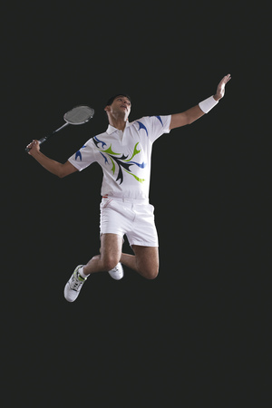 Young male player holding badminton racket while jumping in mid-air