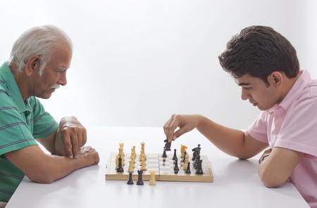 jugando ajedrez: Grandfather and grandson playing chess Foto de archivo