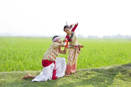 Bihu man blowing on a pepa while Bihu woman dances to his tune Stock Photo