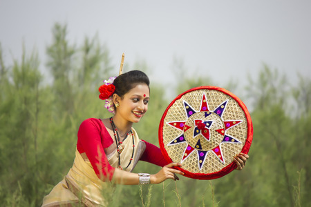 Bihu dancer holding a jaapi Stock Photo