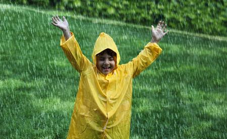 Cheerful boy wearing raincoat enjoying in rain Stock Photo