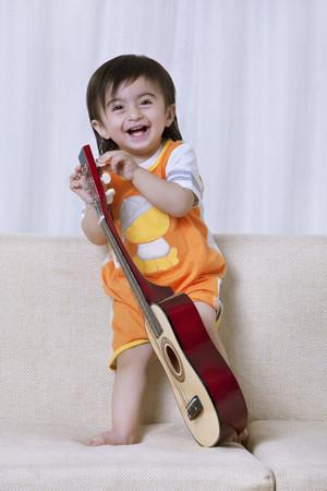 Little boy having fun with a guitar Stock Photo