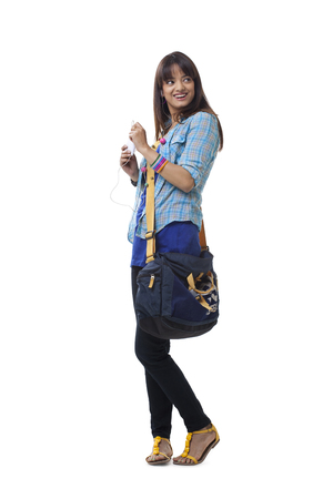 mp3 player: Full length of young woman with backpack listening music over white background