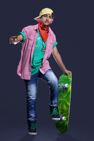 Full length of teenage boy posing with skateboard against black background Stock Photo