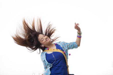 Beautiful young woman enjoying music white swinging hair over white background Stock Photo