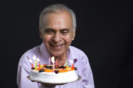 Smiling senior man looking at cake