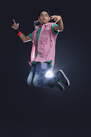 Funky teenage boy jumping in air showing rock and roll sign against black background