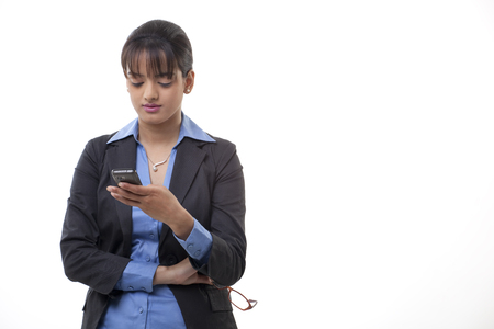 welldressed: Young female executive reading text message over white background