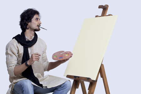 kurta: Young man sitting next to easel with paintbrush in mouth against colored background