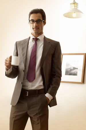 three persons only: Portrait of young businessman having coffee with hand in pocket