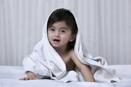only 3 people: Little boy with a towel around his body on a bed