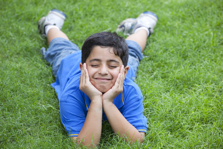 Smiling young boy lying on grass Stock Photo