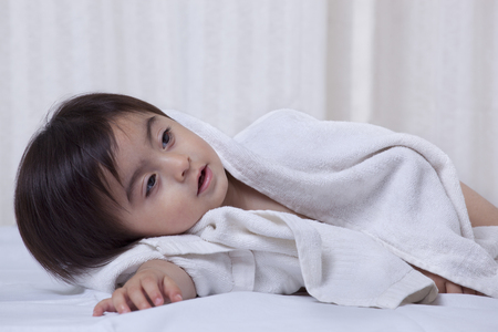 Little boy wrapped in a towel on a bed Stock Photo