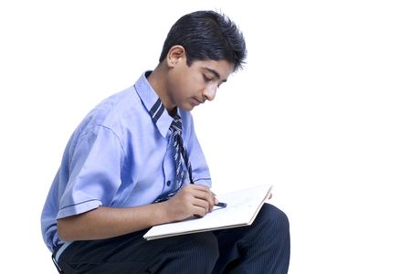 Young teenage boy drawing in book against white background