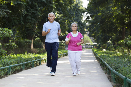 Elderly couple jogging in park