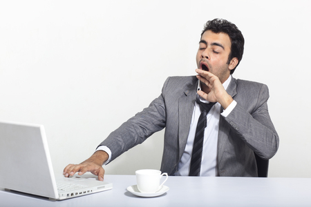 tiredness: Businessman yawning at work