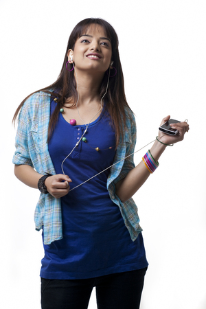 mp3: Young woman listening to music on white background