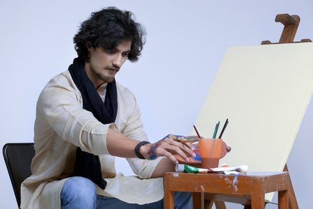 kurta: Young artist sitting near easel against colored background