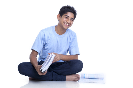 Smiling teenage boy sitting on floor with books against white background Stock Photo