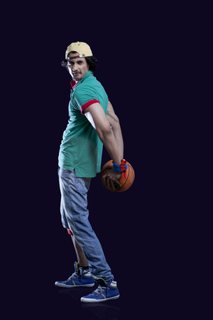 fashion photos: Full length of a young man holding basket ball behind his back against black background