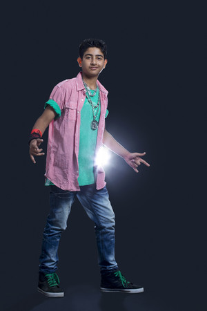 Full length of a confident teenage boy dancing against black background
