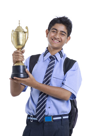 Portrait of teenage boy holding winning trophy against white background Stock Photo