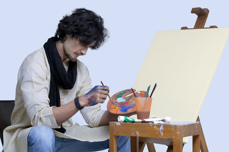 kurta: Young artist mixing colors against colored background Stock Photo