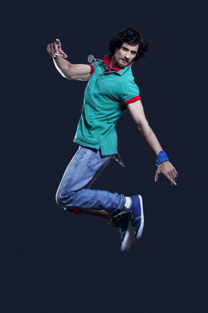 fashion photos: Young man jumping in mid air against black background
