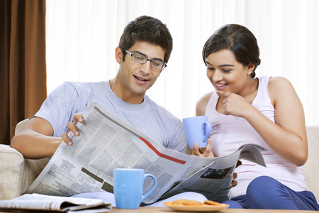 Young couple having coffee while reading newspaper