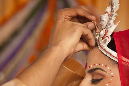 west bengal: Bengali groom putting sindoor on brides forehead
