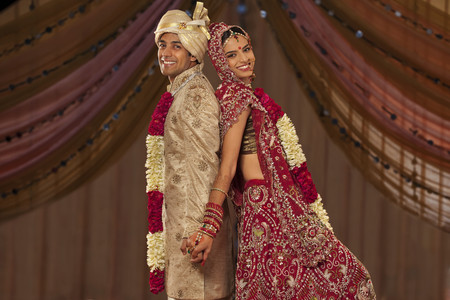 Portrait of newly married Indian couple holding hands