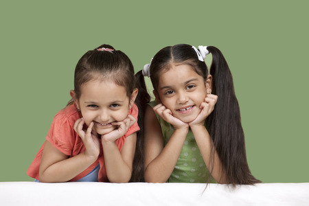 Portrait of smiling girls over colored background Stock Photo