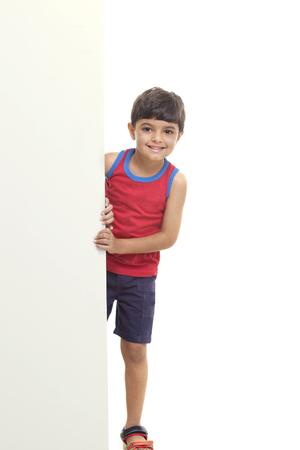 Portrait of boy standing by billboard