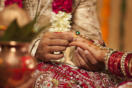 Close-up of a groom putting a wedding ring on a bride