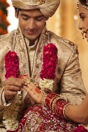 Indian groom putting a wedding ring on a bride