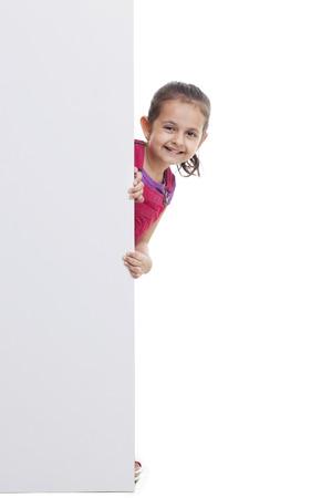 Playful little girl peeking through white board Stock Photo