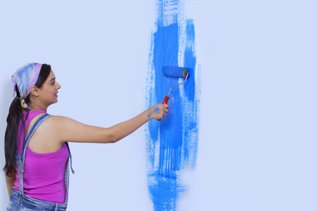 roller: Young woman painting her home wall Stock Photo