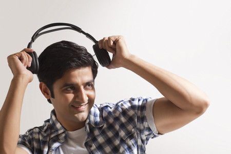 Handsome young man holding headphones and smiling Stock Photo