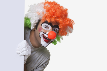 peep: Male clown in tricolor wig smiling over white background