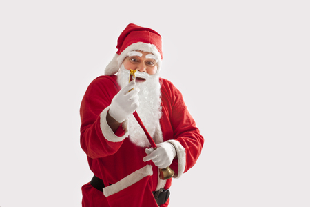 Surprised Santa Claus looking at chocolate over colored background Stock Photo