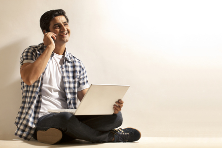 Handsome young man with laptop talking on cell phone Stock Photo
