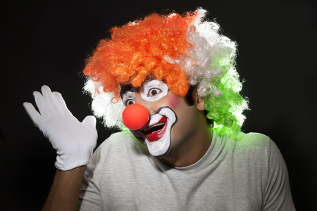 entertainers: Smiling male joker gesturing over black background