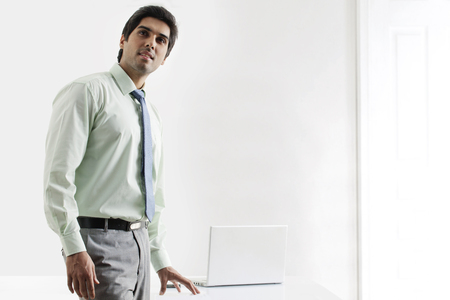 three persons only: Confident businessman standing nearby laptop