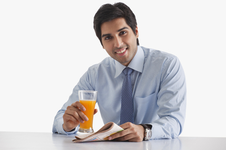 welldressed: Portrait of handsome young businessman with newspaper and glass of juice over white background Stock Photo