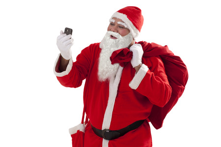 one mature man only: Front view of Santa Claus looking at mobile phone while carrying sack of Christmas presents Stock Photo